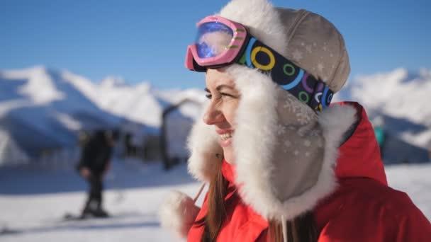 Nahaufnahme einer müden, aber glücklichen Skifahrerin im Skigebiet, die die wunderschöne Winterlandschaft bewundert.