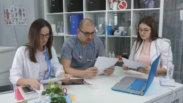 Gesundheitswesen, Medizin: Expertenteam bei der Untersuchung von medizinischen Untersuchungen in einer Arztpraxis. drei Ärzte am Schreibtisch im Beratungsbüro.