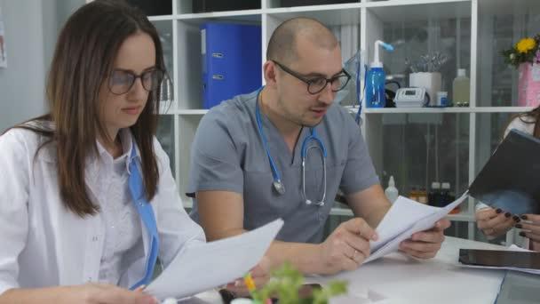 Team von Ärzten, die mit einem Treffen im Büro. Drei Ärzte am Schreibtisch im Büro des Rates