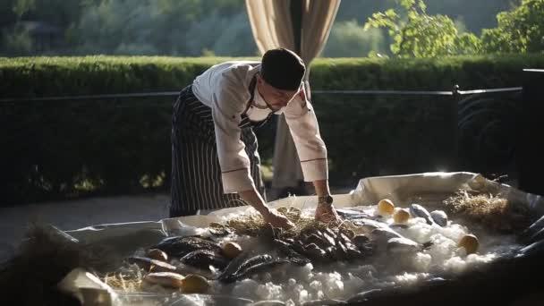 Kuchař dá čerstvé ústřice a ryby na ledě. Detail