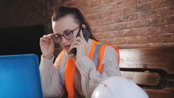 Žena pracující ve skladu na notebooku a mluví o telefonu