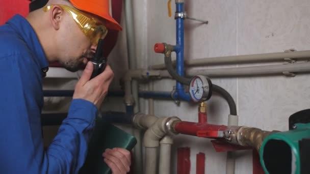 Inženýr posílá rádiem údaje naměřené v prostoru trubice. Kontrola topného systému a dodávky zemního plynu.