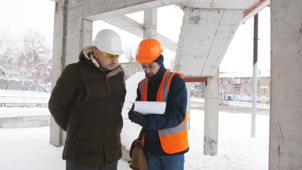 Egy mérnök és a tanfelügyelő, hogy megvitassák a téli havas építkezésen építési terv.