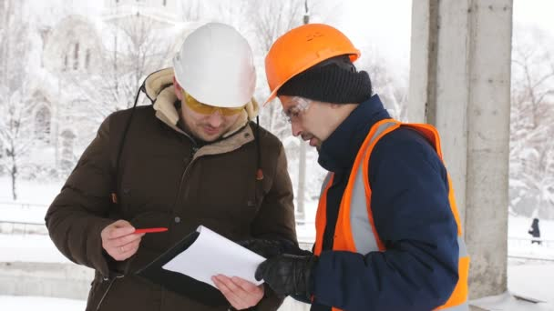 An engineer and superintendent to discuss a plan of construction on a snowy construction site in winter.