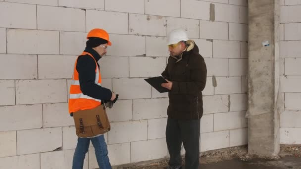 Engineer and foreman at construction site in winter, to discuss documentation to the construction site.