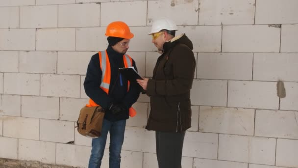 A mérnök ellenőrzi a haladás-ra építőipari építkezésen télen. Beszél az építkezésen a művezető mérnök.