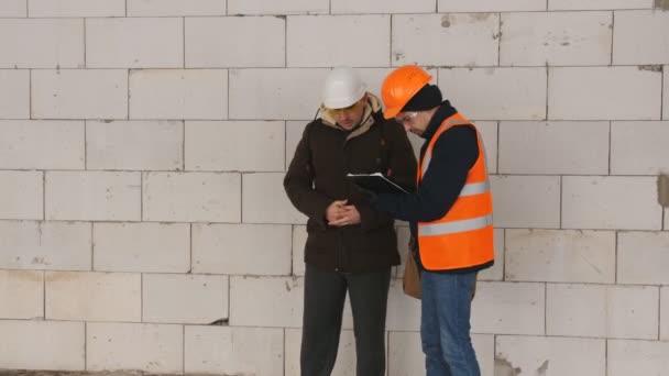 Inženýr a foreman na staveništi v zimě, diskutovat o dokumentaci na staveniště.
