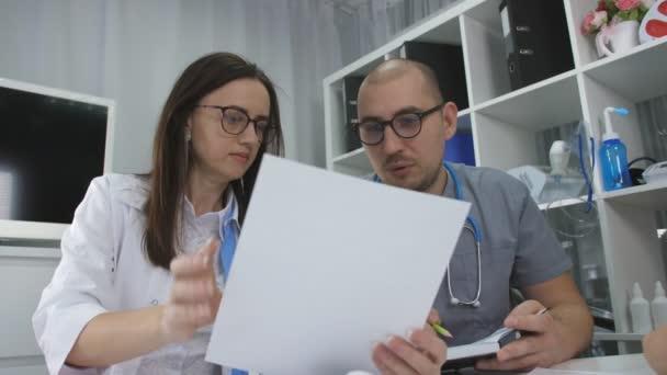 Diskuse lékařů na klinice úřadu. Lékař muže a dvě ženy v kanceláři kliniky jsou setkání