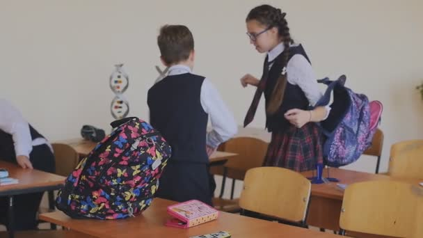 Schoolchildren in school uniform puts on a backpack to go home. Slow motion. High school students in the classroom