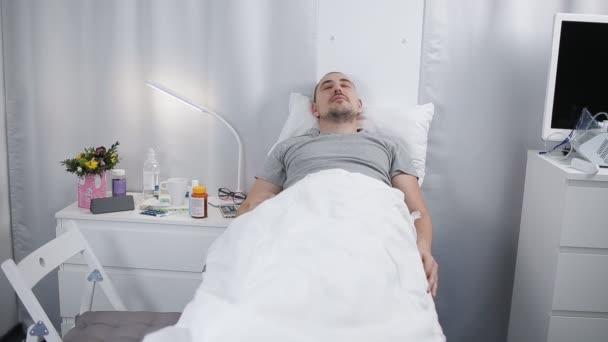 Egy ember fekszik egy kórházi szobában egy ágy. A beteg beteg alszik egy ágyban egy osztályon.