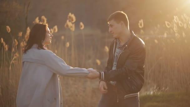 Mladý šťastný pár v parku při západu slunce s zábavné a užívat si života. Milující pár splňuje společně západ slunce v romantickém prostředí