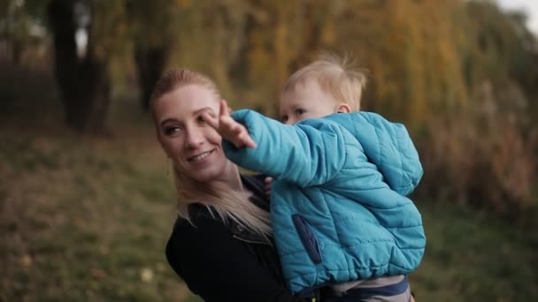 Closeup footage of happy young mother hugging and throwing here baby son at autumn park
