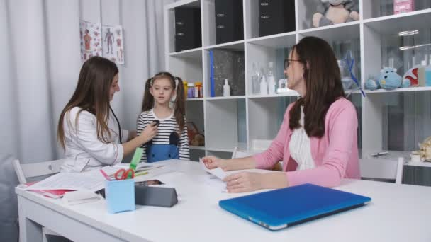Mutter und junge Tochter zum Arzt. Ärztin verwendet ein Stethoskop, um niedliche kleine Mädchen im Krankenhaus zu untersuchen. In Zeitlupe