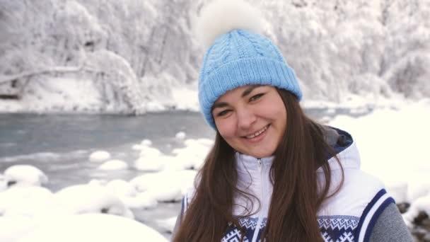 Portrét krásné ženy v zimním lese nedaleko horské řeky. Dívka se dívá do kamery s úsměvem a směje se.