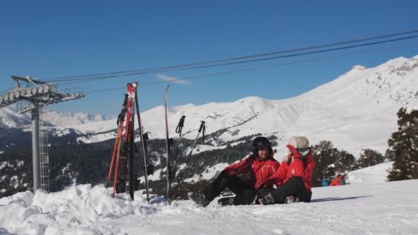 Pár lyžařů baví sedět na sněhu. Mají dobrou náladu, tráví tento čas spolu.