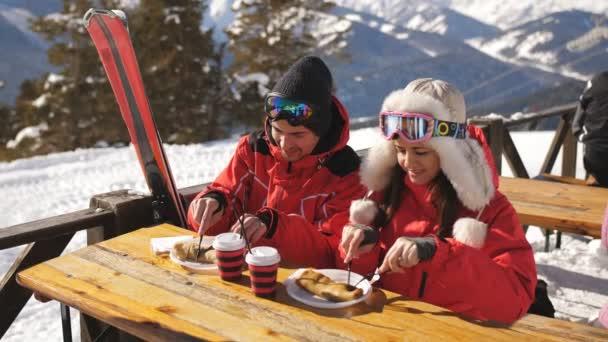 Paar Skifahrer auf dem Berg beim Mittagessen im Restaurant im Freien.