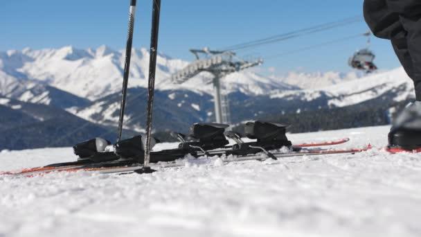 Oprava lyžařských bot. Lyžování zavřít. Dívka zipy po lyžařské boty a hole nohy v držáku na lyže před sestupně na sjezdovky.