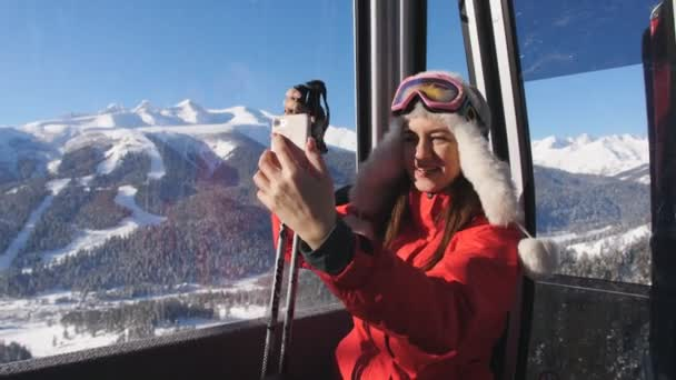 Woman making selfie on smartphone in the cabin ski lift.