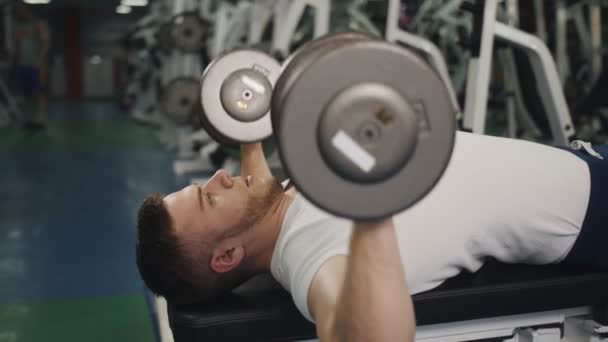 Man performs exercise lifting dumbbells for biceps lying on bench close-up