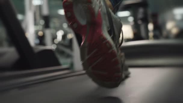 Slow motion záběry údajně ženské nohy v tenisky běží na běžeckém pásu.