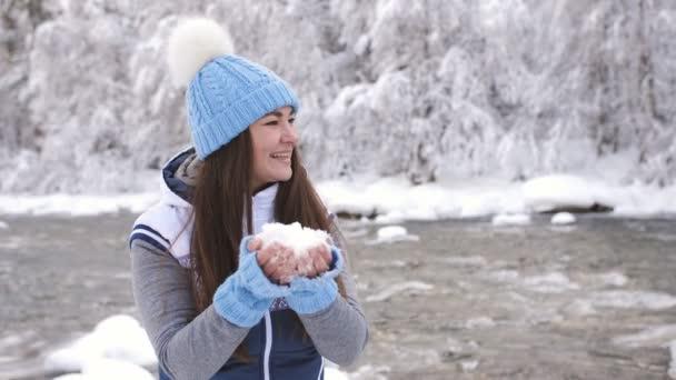 Žena poblíž řeky zimě těší mrazivé ráno, vyvolá sníh nad sebe a spřádání od štěstí.