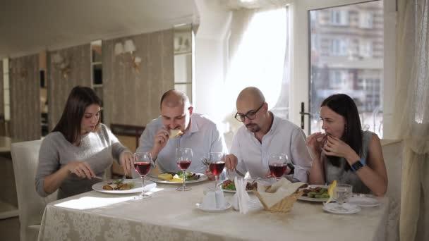Čtyři přátelé v restauraci, jíst maso a pít červené víno ve skle.