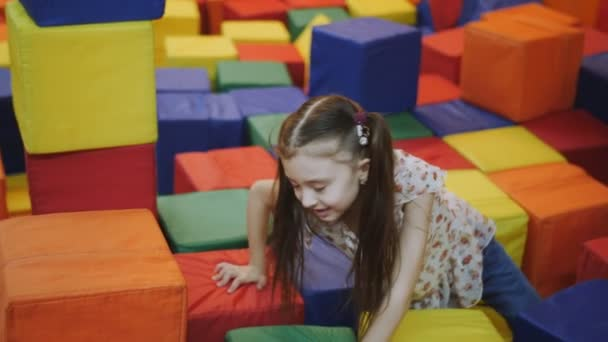 Little Devochka play in a trampoline center with soft cubes.