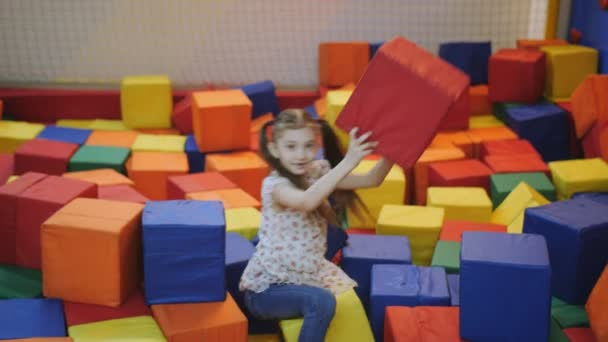The girl in the trampoline centre is building a castle in soft multi-colored cubes.