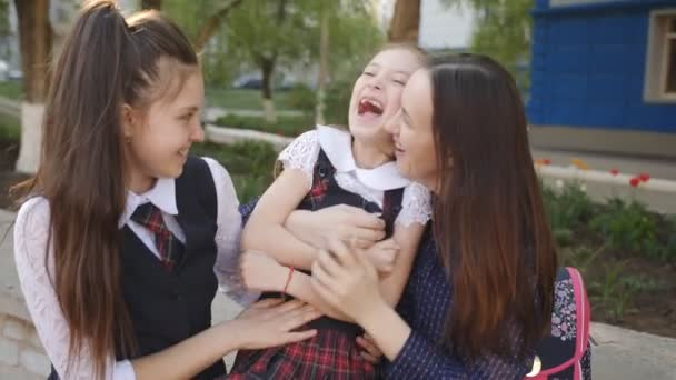 Happy mother with daughters outside having fun and laughing together.