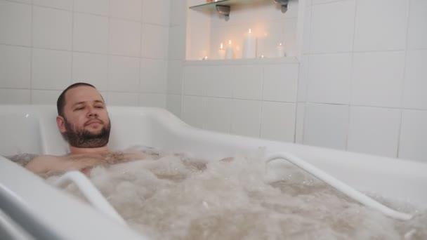 Az ember a masszázs Spa a pezsgőfürdőben. Egy ember a fürdőben, amelynek rekreációs hidroterápiás vízsugár masszázs fizikai terapeuta.