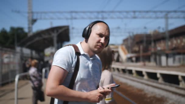 Male tourist standing on the platform waiting for the train and listening to music on headphones.