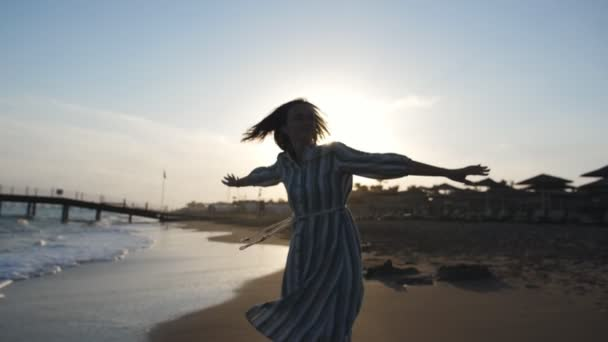 Girl spinning with excitement in sunlight on beach