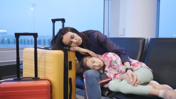 A mother hugging her little daughter and sleeping on the chairs at the airport terminal while waiting for her next flight