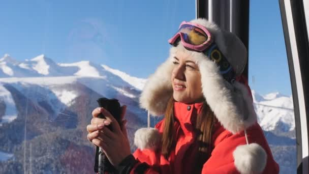 Zavřená dívka v uzavřeném lyžařském výtahu stoupá na vrchol hory.