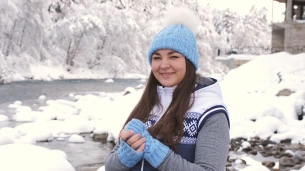 Portrét krásné ženy v zimním lese nedaleko horské řeky. Žena, mnul si ruce a dýchal teplý vzduch na rukavice.