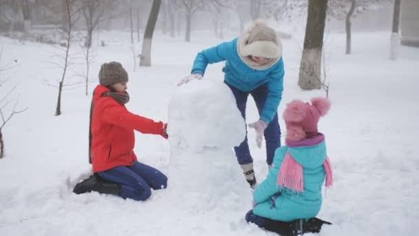 Eltern und Kinder spielen im Schnee. Mutter und zwei Töchter formen im Winter einen Schneemann.
