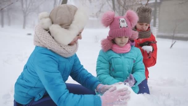 Anya és két lánya farag hóember. Egy boldog család teszi egy hóember kívül télen.