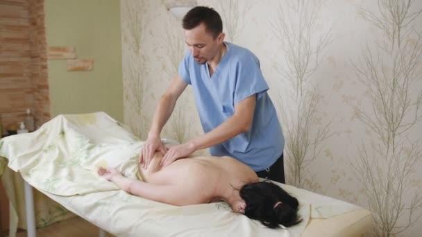 Mužské ruce dělají masáž na zádech samičky. Při léčbě lázeňského masáží je uklidňující žena.