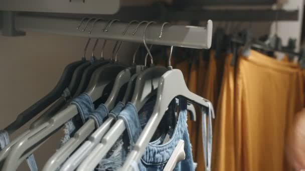 Širokou nabídku Dámské džínové bundy zavěšení na ramínko. Žena se rozhodne její oblečení v obchodě. Rukou zblízka