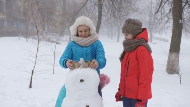 Mutter und zwei Töchter formen gemeinsam Schimmel aus Schneemensch. Winter-Familienspiele im Freien.
