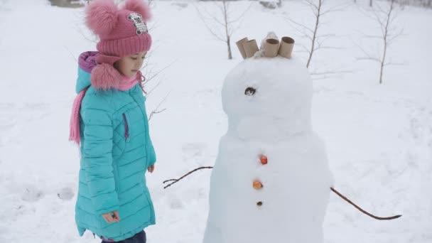 Malá holčička zdobí sněsníka. Zimní hry.