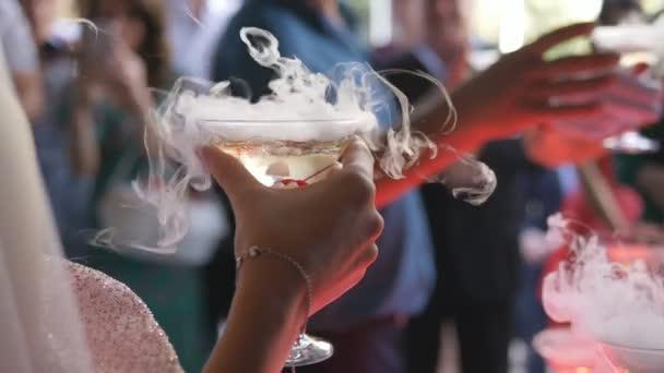 Die Braut und der Bräutigam halten Champagnergläser dampfend. Trockeneis im Glas mit Champagner in den Händen des Brautpaars.