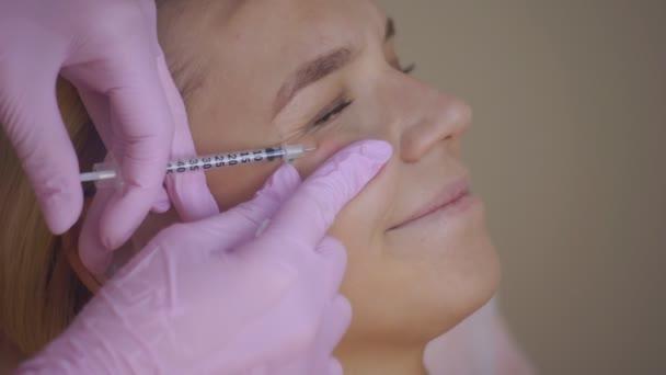 Nahaufnahme eines Kosmetologen, der einem jungen Mädchen Anti-Aging-Injektionen macht, Zeitlupe. die Kosmetikerin führt die biorevitalisierende Prozedur im Gesicht durch.