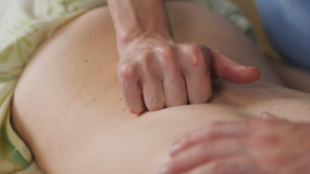 Uzavření rukou maséra, aby masíroval zadní část ženy.