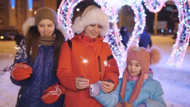 Matka se dvěma dcerami se baví s jiskříčky v rukách zábavného večera v centru města na Štědrý den.