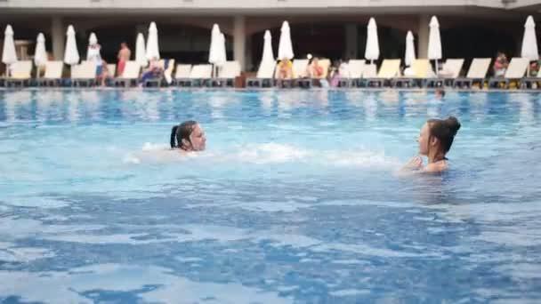 Mutter und Tochter googeln herum und bespritzen sich gegenseitig mit Wasser im Pool.
