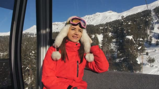 Girl in a ski suit and ski goggles rides in the gondola on the cable car. The ski resort.