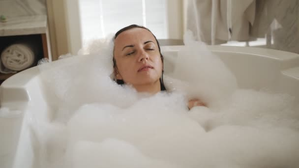 Šťastná žena si vychutná koupel plnou pěny. Krásná žena požívá lázně doma