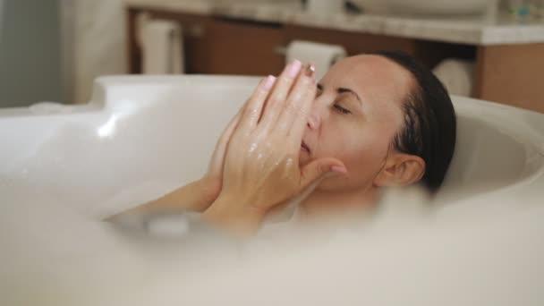 Krásná žena relaxační ve vaně plné pěny