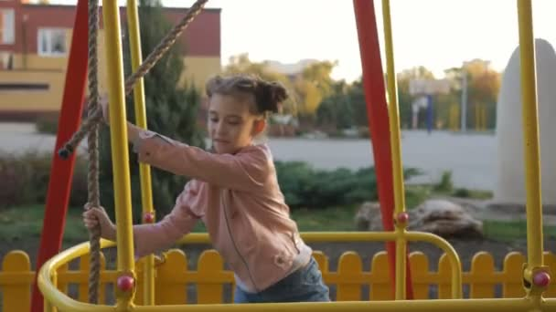 A little girl of 7 years standing swinging on the big swings in the Playground.